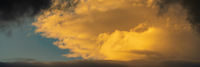 Panorama dramatic clouds illuminated rising of sun in blue sky. Natural weather, meteorology