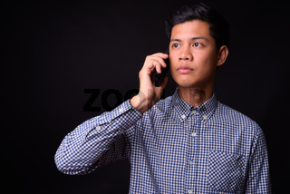 Portrait of young Asian businessman against black background