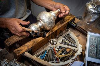 Jewellery maker working in workshop crafting homemade silver vase.