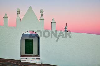 Auf der Kanareninsel Lanzarote steht hinter dieser Mauer eine Kirche. Beim Sonnenuntergang ein wundervoller Anblick