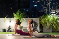 Asian women do yoga in city at night