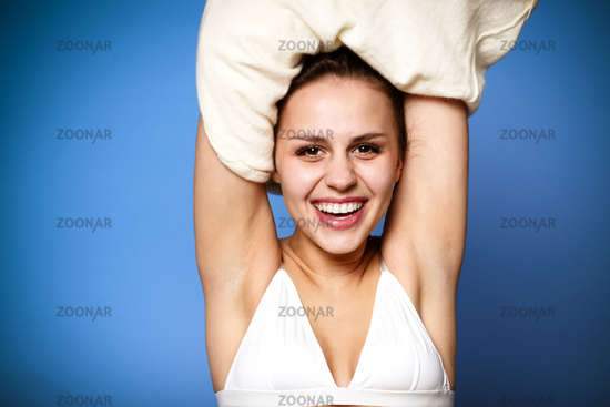 Glad young female smiling and taking off soft and warm sweater against blue background
