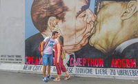 young couple kissing in front of mural painting at east side gallery
