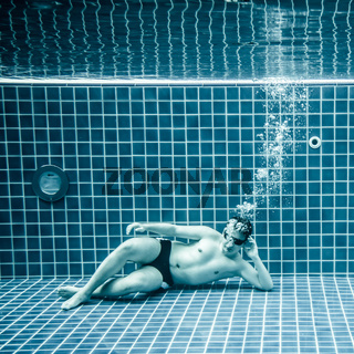 Persons lies under water in a swimming pool