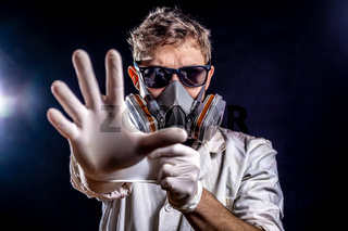 Caucasian male with dark sunglasses wearing half face respirator or gas mask reaching hand towards camera, dark background with dramatic lighting effects in dusty enviroment. Virus fear concept.