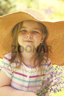 Happy little girl blonde with long hair at sunset in lavender field