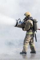 One firefighter extinguish fire from fire hose, using firefighting water-foam barrel