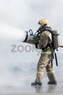 One firefighter extinguish fire from fire hose, using firefighting water-foam barrel with air-mechanical foam