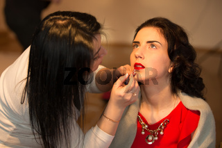 Belarus, Gomel, February 13, 2018. School of Morgan models. Model tests. A professional make-up artist does make-up on the face. Dye your lips bright red lipstick