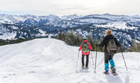 Senior couple is snowshoe hiking in alpine snow winter mountains. Allgau, Bavaria, Germany.
