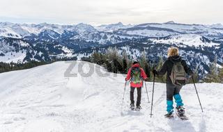 Senior couple is snowshoe hiking in alpine snow winter mountains. Allgau, Bavaria, Germany.