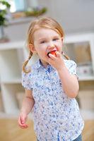 Mädchen beißt in eine frische Erdbeere