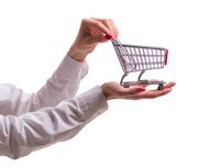 Hand holding shopping cart isolated on white