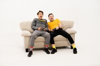 Friends playing video games while spend time together sitting on the small sofa looking at the camera isolated on white background. Group of guys sitting on couch and communicates on white