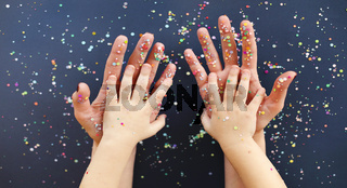 Hands of woman and kid in colorful confetti