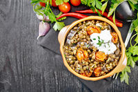 Lentils with eggplant and tomatoes in bowl on dark board top