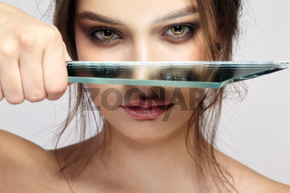 Portrait of a beautiful girl with a mirror splinter near eyes.