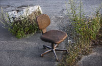 An old chair has been discarded. . .