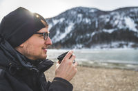 Outdoor wilderness adventure: Caucasian man is drinking a metal cup of tea