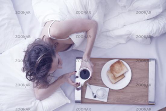 Woman has breakfast in the bed