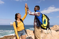 Fit afrcan american couple wearing backpacks high fiving hiking on the coast