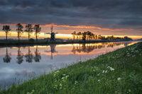 beautiful sunrise in Dutch farmland with windmill
