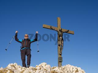 Bergsteiger in Siegerpose am Gipfel des Berchtesgadener Hochthron