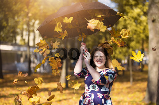 Beautiful young woman in an autumn park with an umbrella from which yellow leaves are falling.