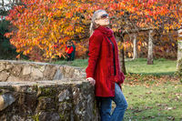 Woman rests against rustic stone fence among autumn trees