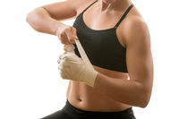 Young muscular strong woman putting on bandage, isolated on white background. Martial arts, fitness, weight loss concept.