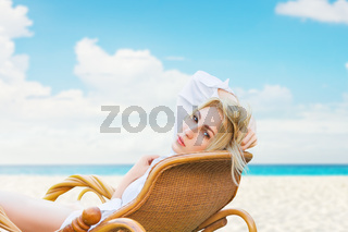 Young beautiful blonde woman enjoying tropical sea view while sitting on chair at luxury resort lounge