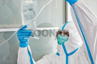 Arzt auf Intensivstation bereitet Infusion für Covid-19 Patient vor