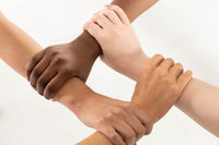 Each of the four hands is clasped around the friend's wrist. One hand grips the other, and so on. Young girl's hands.