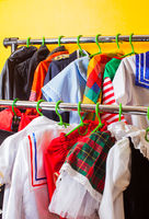 Rack with many cool holiday costumes for kids on hangers at children fashion showroom. Rental service in the cloth shop.