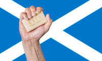 Caucasian male hand holding soap with words: Wash Your Hands against a Scottish flag background