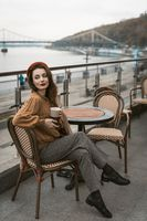 Sitting sideways turned Parisian young woman in restaurant terrace. Portrait of stylish young woman wearing autumn coat and red beret outdoors