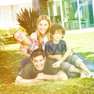 Glückliche Familie im Sommer vor dem Haus