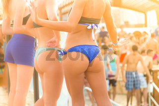 Sexy hot girls wearing brazilian bikini dancing on a beach party event in sunset. Crowd dancing and partying at poolside in background. Summer electronic music festival. Hot summer party vibe