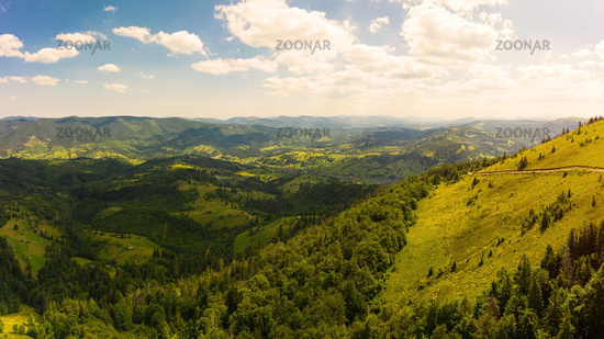Aerial drone view of picturesque nature with green coniferous forests on the slopes of the mountains