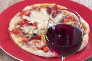 Nahaufnahme von Rotwein mit Pizza