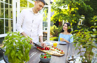 Young couple cooking sandwiches in garden