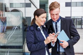 Geschäftsleute schauen zusammen auf Smartphone