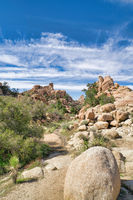 Huge rocks and hiking pathway at Joshua Tree National Park on a sunny day