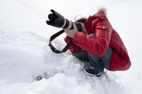 A photographer with a large lens takes pictures while sitting in the snow.