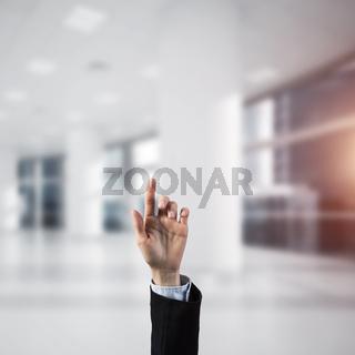 Choosing gesture of businessperson in elegant modern interior in sunshine light