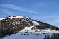 Snowy ski slope with ski-lifts, traces and forest in high winter mountains at sunny morning