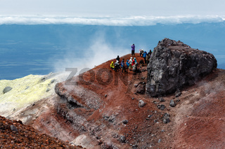 Group of travelers and tourists in summit crater of active volcano