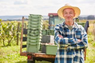 Erfolgreicher Weinbauer mit verschränkten Armen