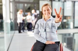 Geschäftsfrau im Rollstuhl macht Victory Zeichen