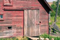 Front of an old abandoned red barn with door and sliding door
